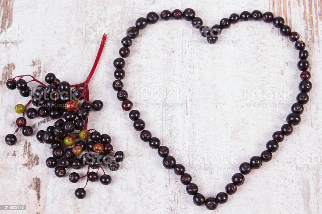 Heart of fresh elderberry on old wooden background stock photo