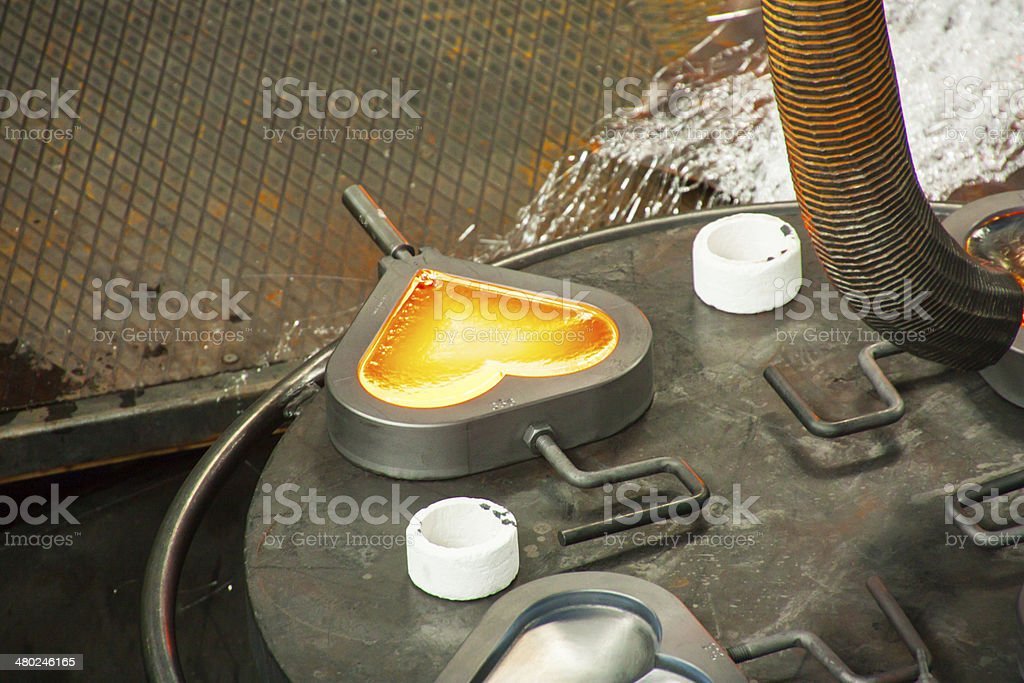 Heart of liquid glass Heart of glass poured into a mold in a glass factory. Art And Craft Stock Photo