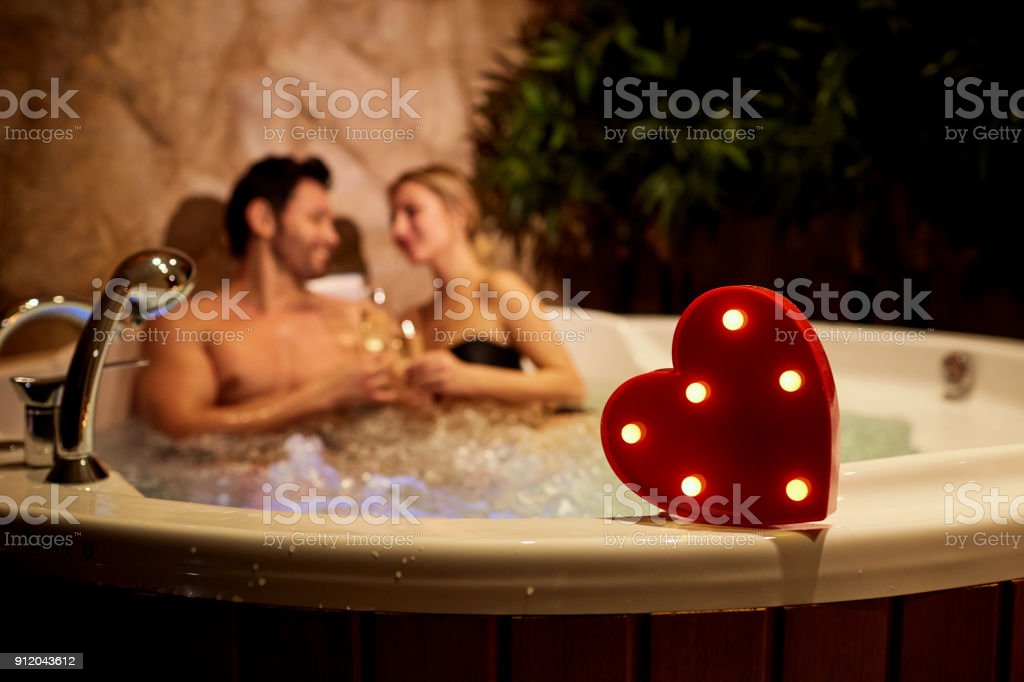 Heart on a background of a romantic couple with champagne in the stock photo