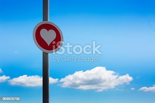 Heart sign on a pole next to a road