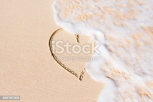 istock Heart on sand beach being washed away 526762305
