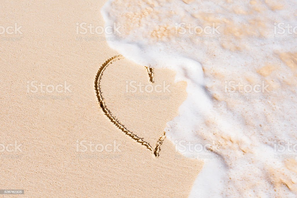 Heart on sand beach being washed away stock photo