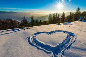 Winter mountain landscape with snowly fir. Winter mountain heart sign on a sunny day.