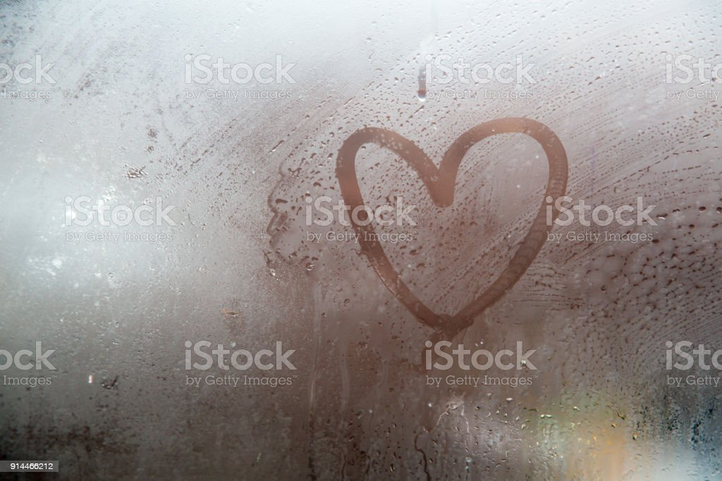 A heart painted on a misted window.Heart on misted glass. stock photo