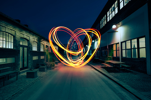 With light, a heart is painted in the air in the middle of a small street between two industrial buildings.