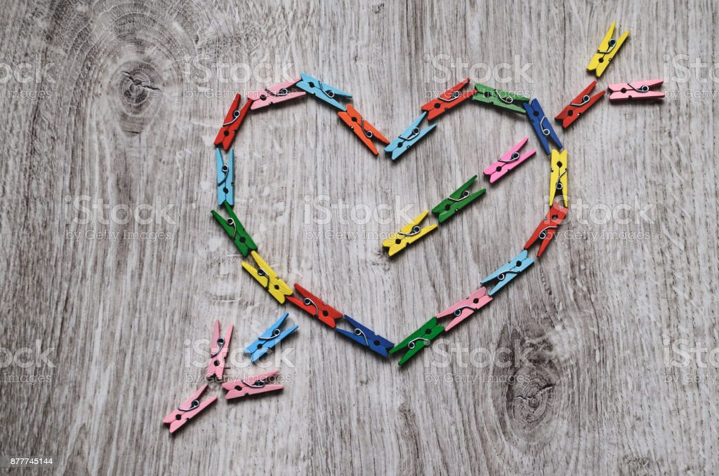 Heart pierced by an arrow made of wooden clothespins stock photo