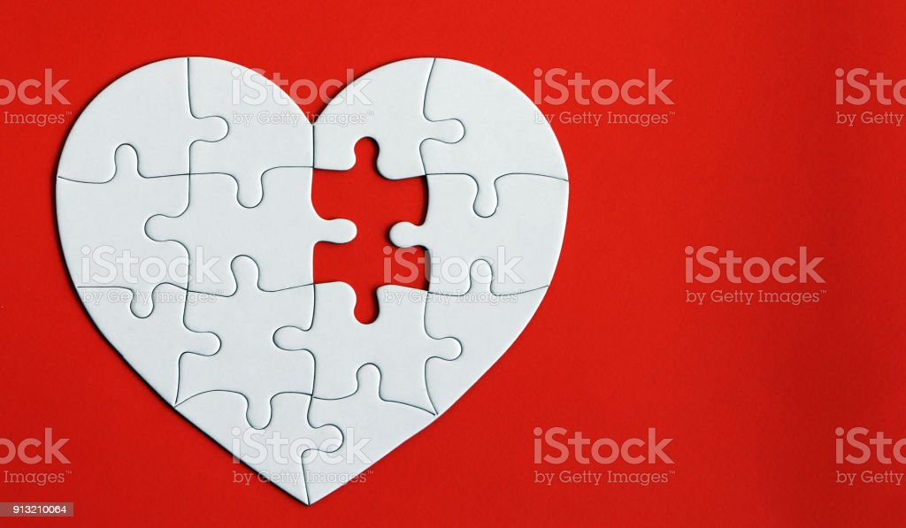 Heart puzzle on the red background. A missing piece of the heart puzzle. stock photo
