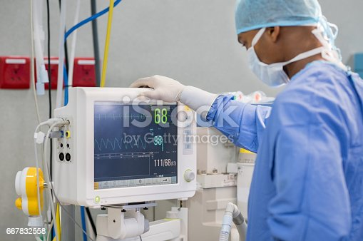 African surgeon keeping track of vital functions of the body during cardiac surgery. Surgeon looking at medical monitor during surgery. Doctor checking monitor for patient health status.