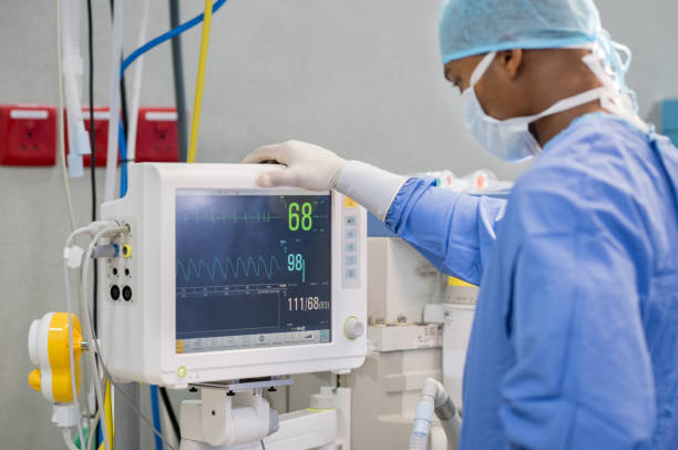 Heart rate monitor in hospital theater African surgeon keeping track of vital functions of the body during cardiac surgery. Surgeon looking at medical monitor during surgery. Doctor checking monitor for patient health status. life support machine stock pictures, royalty-free photos & images