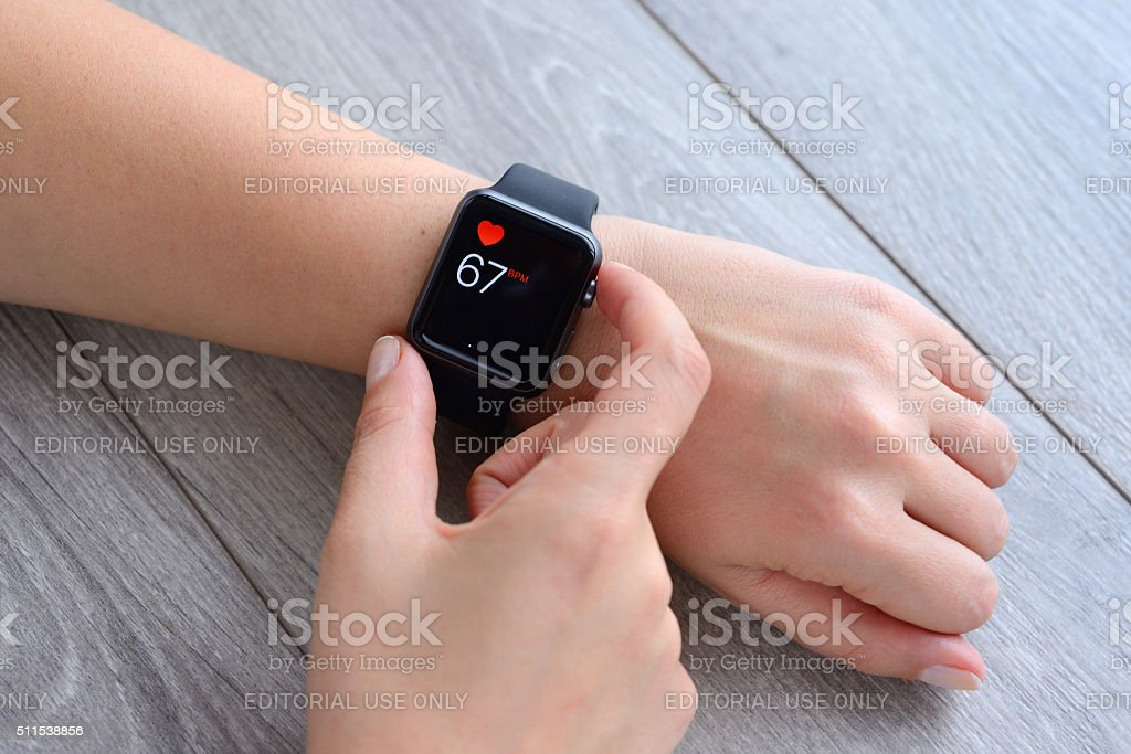 Heart rate on Apple Watch İstanbul, Turkey - January 16, 2016: Hand wearing an Apple Watch displaying heart rate on a desk. Apple Watch is a smart watch, devices developed by Apple Inc. Active Lifestyle Stock Photo