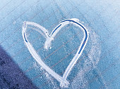 A heart symbol in the icy surface of a blue windshield