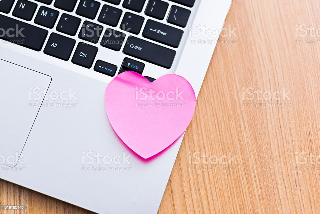 Heart shape adhesive note on laptop stock photo