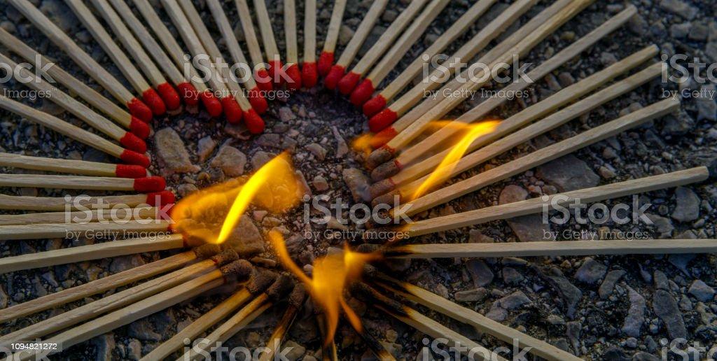 Heart shape arranged with burning matches