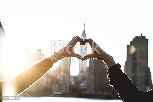 Heart shape with female hands on the sunlight.