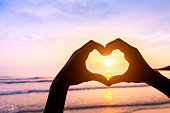 Shape of heart done with silhouette of hands on a beach with sunset sun and colors - Symbol of love - Concept about romantic travels, summer, valentine, honeymoon