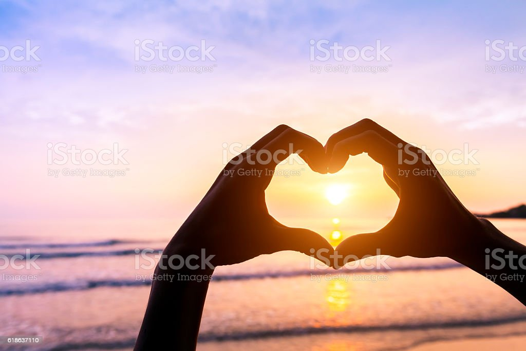 Heart shape, beach and sunset, symbol of romantic travels, love stock photo