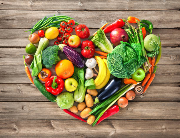 Heart shape by various vegetables and fruits Heart shape by various vegetables and fruits on wooden table. Healthy food concept healthy heart stock pictures, royalty-free photos & images
