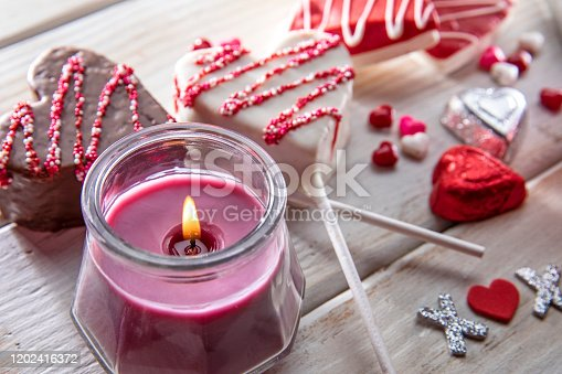 This is a photograph of two chocolate heart shape cookies in red icing on a retro white table with a gift. surrounded by foil chocolates This is a creative homemade craft of a full frame image symbolizing Valentine's Day and love