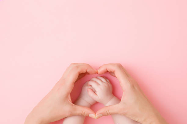 Heart shape created from young mother hands. Infant arms in middle. Pink pastel table background. Lovely emotional, sentimental moment. Closeup. Empty place for text, quote or sayings. Top down view. Heart shape created from young mother hands. Infant arms in middle. Pink pastel table background. Lovely emotional, sentimental moment. Closeup. Empty place for text, quote or sayings. Top down view. sentimentality stock pictures, royalty-free photos & images