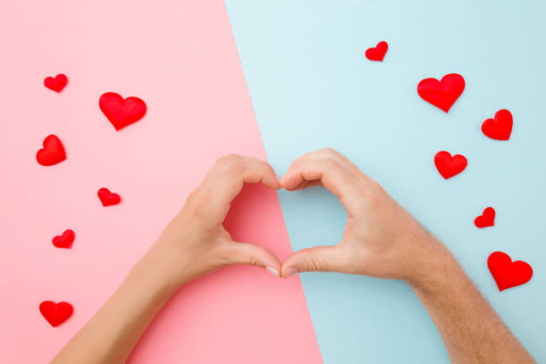 Heart shape created from young woman's and man's hands. Red small hearts around. Pastel pink blue color background. Love and happiness concept. Close up. Top view. Heart shape created from young woman's and man's hands. Red small hearts around. Pastel pink blue color background. Love and happiness concept. Close up. Top view. sentimentality stock pictures, royalty-free photos & images