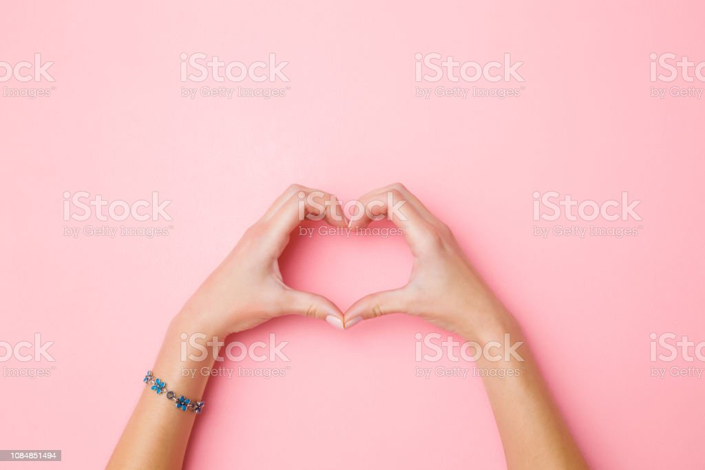 Heart shape created from young woman's hands on pastel pink background. Love and happiness concept. Empty place for emotional, sentimental text, quote or sayings. Closeup. Top view. Heart shape created from young woman's hands on pastel pink background. Love and happiness concept. Empty place for emotional, sentimental text, quote or sayings. Closeup. Top view. Adult Stock Photo