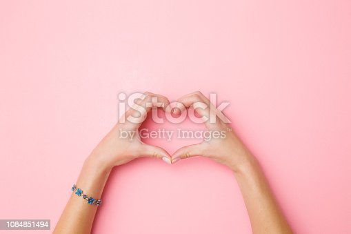 istock Heart shape created from young woman's hands on pastel pink background. Love and happiness concept. Empty place for emotional, sentimental text, quote or sayings. Closeup. Top view. 1084851494