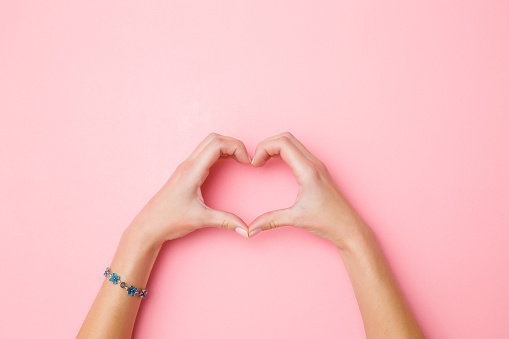 Heart Shape Created From Young Womans Hands On Pastel Pink Background Love And Happiness Concept Empty Place For Emotional Sentimental Text Quote Or Sayings Closeup Top View Stock Photo - Download Image Now