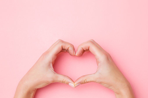 Heart shape created from young woman's hands on pastel pink background. Love and happiness concept. Empty place for emotional, sentimental text, quote or sayings. Closeup.