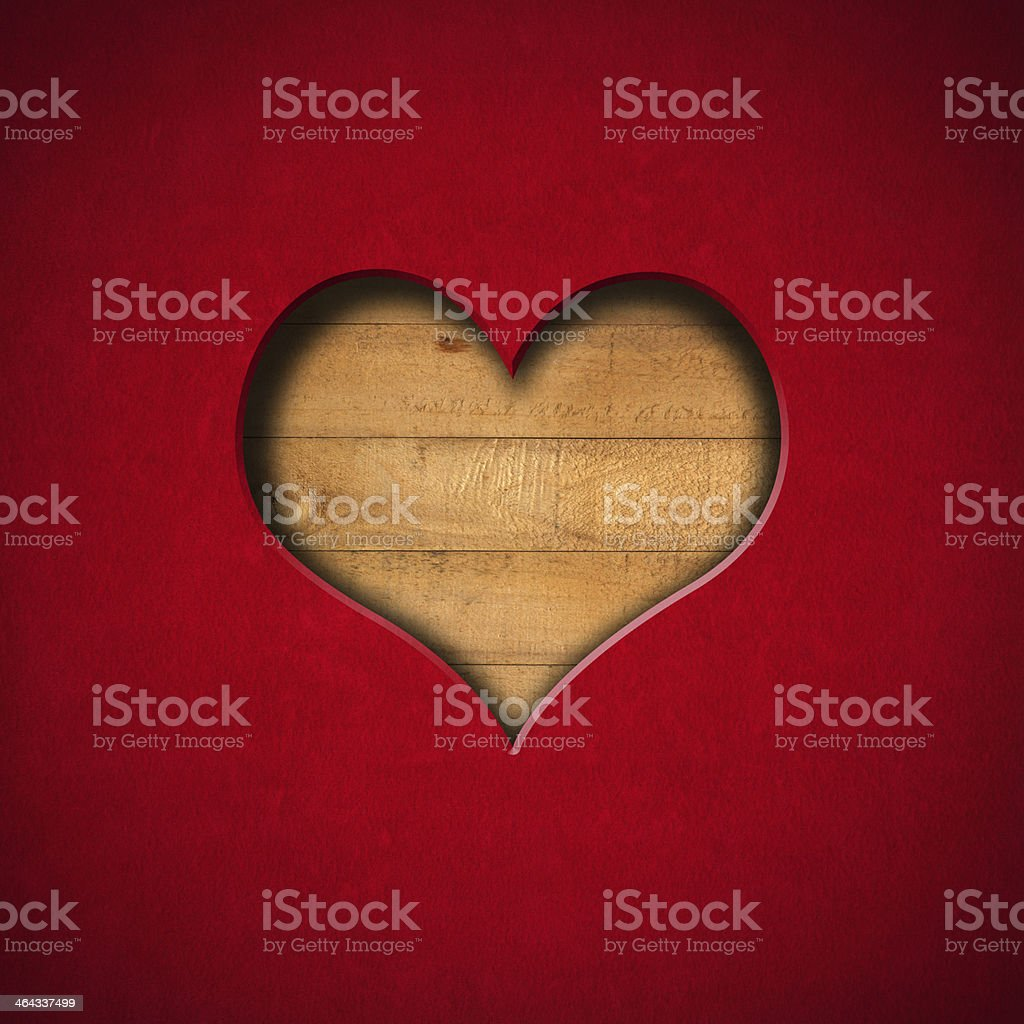 Heart shape cut out of a sheet of red velvet on wood surface stock photo