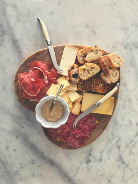 herz-form-schneidebrett mit canapés. gibt es salami, käse, brot und schinken mit einigen hummus. food-liebe-konzept - wurst käse dips stock-fotos und bilder
