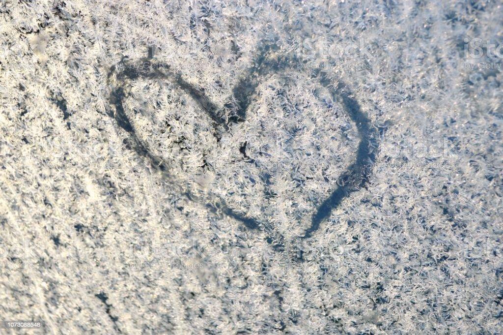 Heart shape drawn on a frozen window stock photo