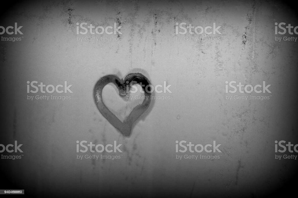 Heart shape drawn on steamy window stock photo