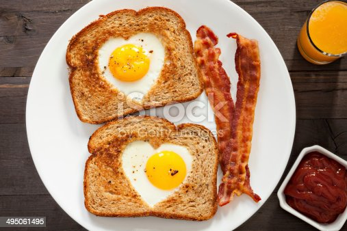 An overhead close up shot of heart shaped eggs inside toast, a couple of bacon strips and fresh squeezed orange juice