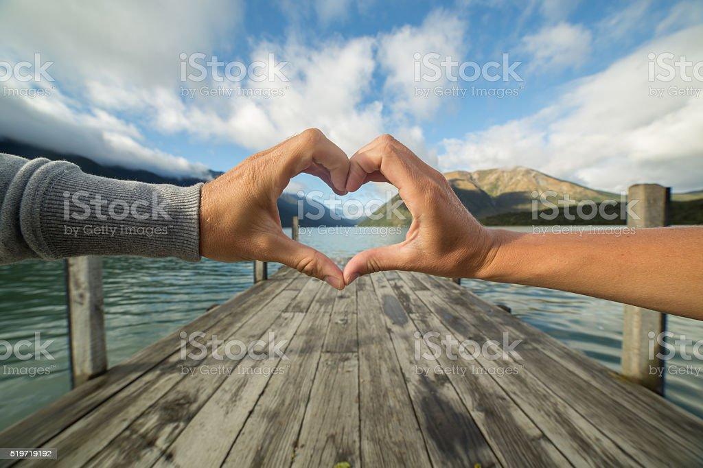 Heart shape finger frame on mountain lake landscape stock photo