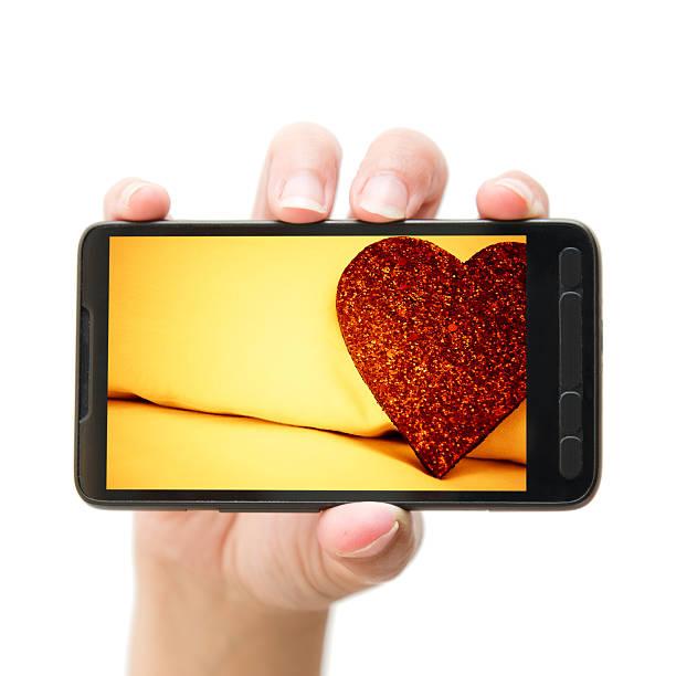 форма сердца святого валентина на мобильный смартфон - hand holding phone стоковые фото и изображения
