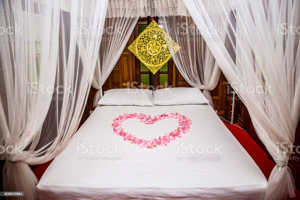 Heart shape from pink rose petals on the white bed. honeymoon suite room decoration. luxury suite. holidays with valentine theme. stock photo