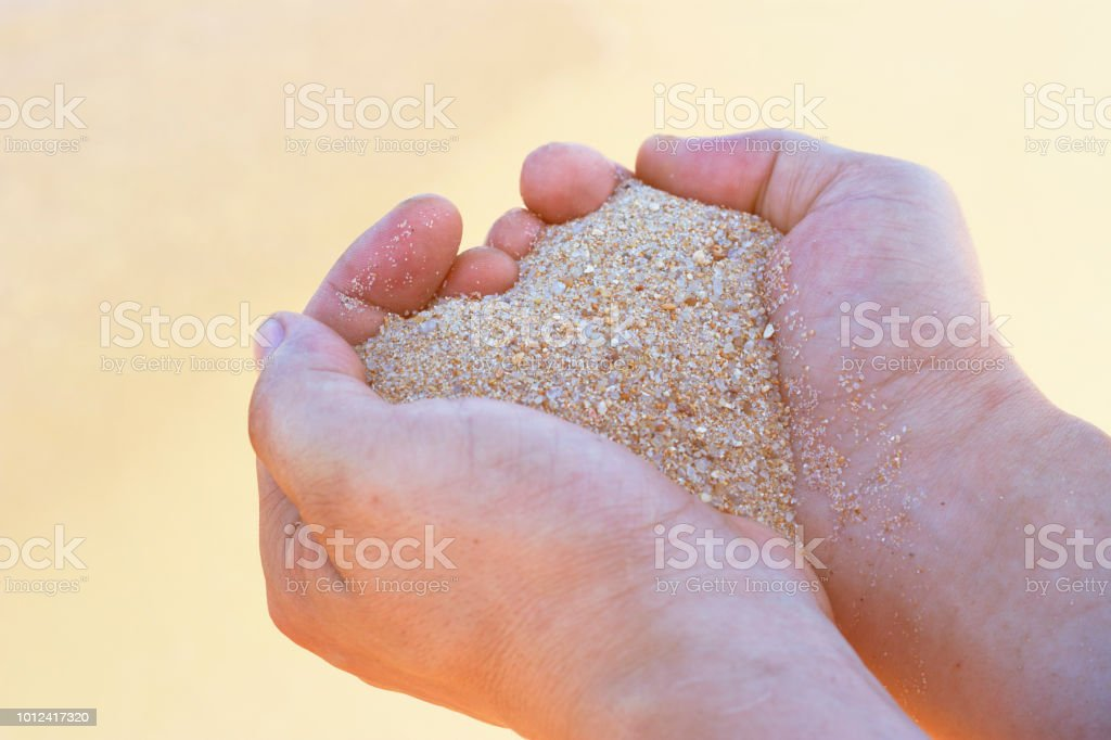 Heart shape from sand in male hands against the background of the sea, Concept of summer, love, vacation.  Toned, soft sunlight