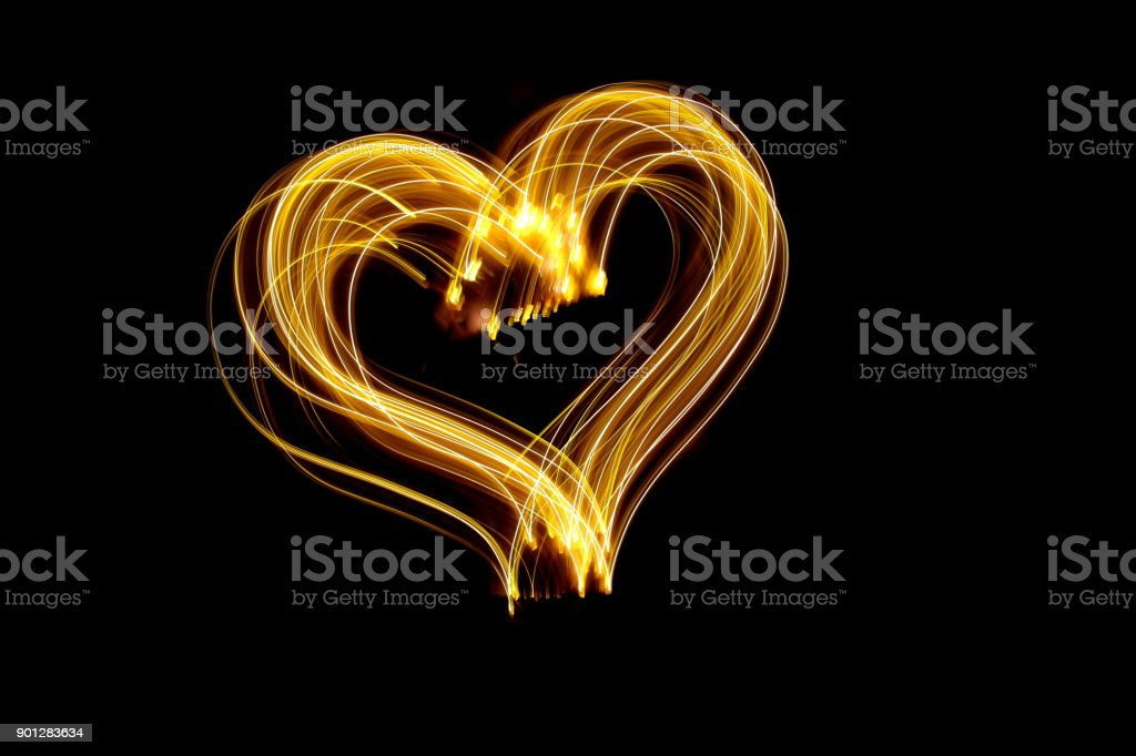 A long exposure photograph of metallic gold fairy lights in a heart...