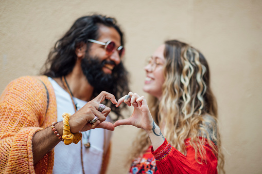 A shot of a mid adult Pakistani man and a young caucasian woman making a heart sign with their hands. They are wearing casual bohemian clothing and accessories and are looking and smiling at each other.