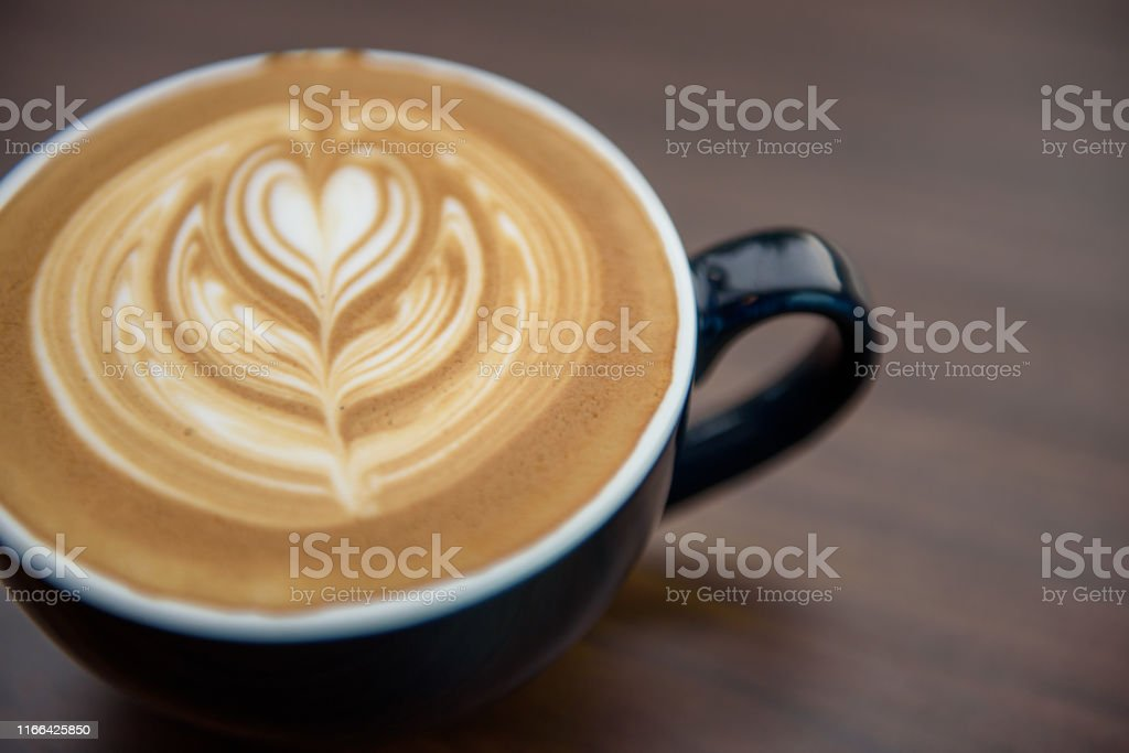Heart shape latte art in black cup on wooden table