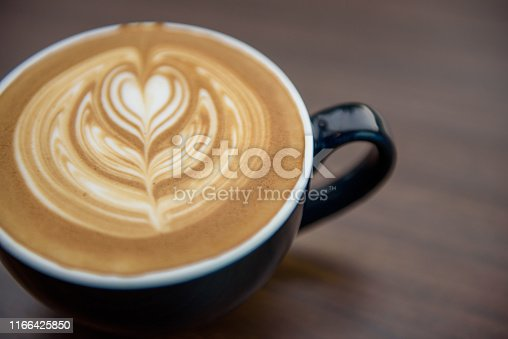 Heart shape latte art in black cup on wooden table