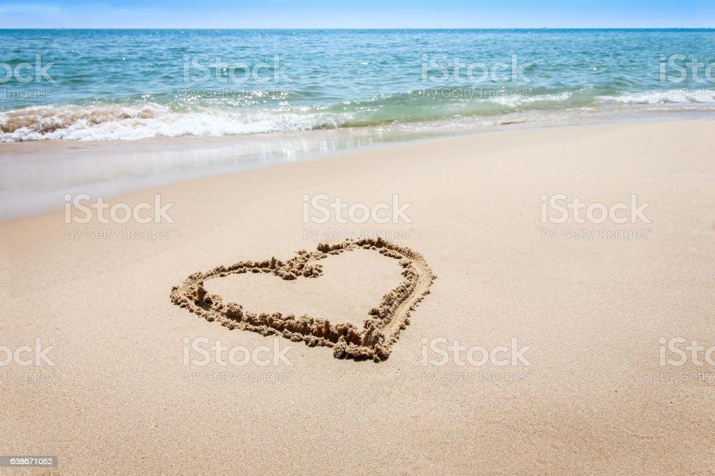 Heart shape, love symbol written at the sand beach stock photo