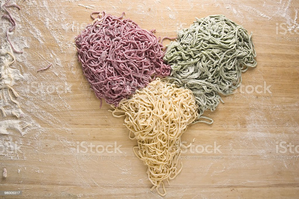 Heart shape made of uncooked fresh spaghetti in three colours royalty free stockfoto