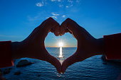 Heart shape made with hands enveloping the Cypriot morning sun in the horizon.