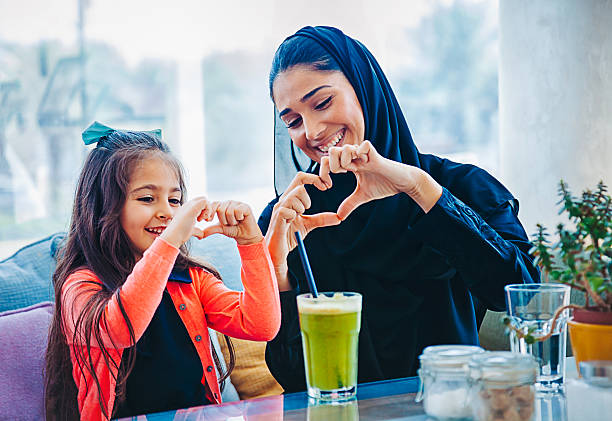 Heart shape made with hands Middle eastern beautiful mother and cute daughter showing forming heart shape symbol making with their fingers hands and smiling at cafe restaurant arabia stock pictures, royalty-free photos & images