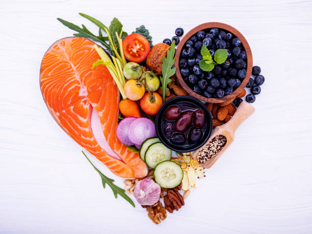 Herzform von ketogene Low Carbs Diät Konzept. Zutaten für gesunde Lebensmittel Auswahl auf weißem Holzhintergrund. Ausgewogene gesunde Inhaltsstoffe von ungesättigten Fetten für Herz und Blutgefäße. – Foto