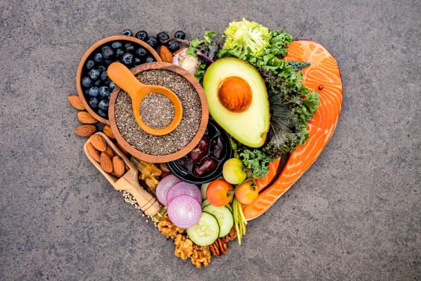 Herzform von ketogene Low Carbs Diät Konzept. Zutaten für gesunde Lebensmittel Auswahl auf dunklem Stein Hintergrund. Ausgewogene gesunde Inhaltsstoffe von ungesättigten Fetten für Herz und Blutgefäße. – Foto