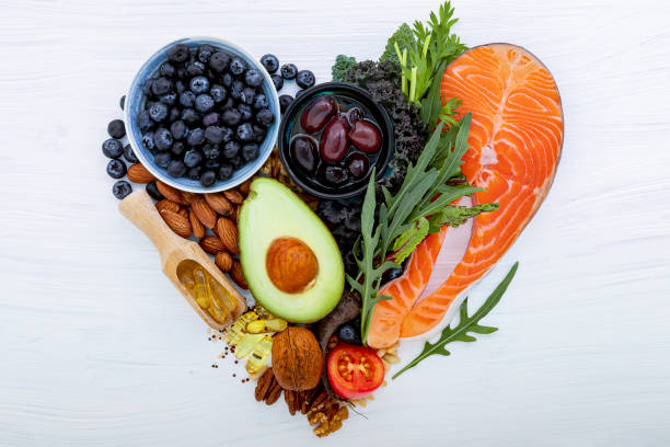 心臟形狀生性低碳水化合物飲食概念。白色木制背景上健康食品選擇的成分。心臟和血管不飽和脂肪的平衡健康成分。 - 健康飲食 個照片及圖片檔