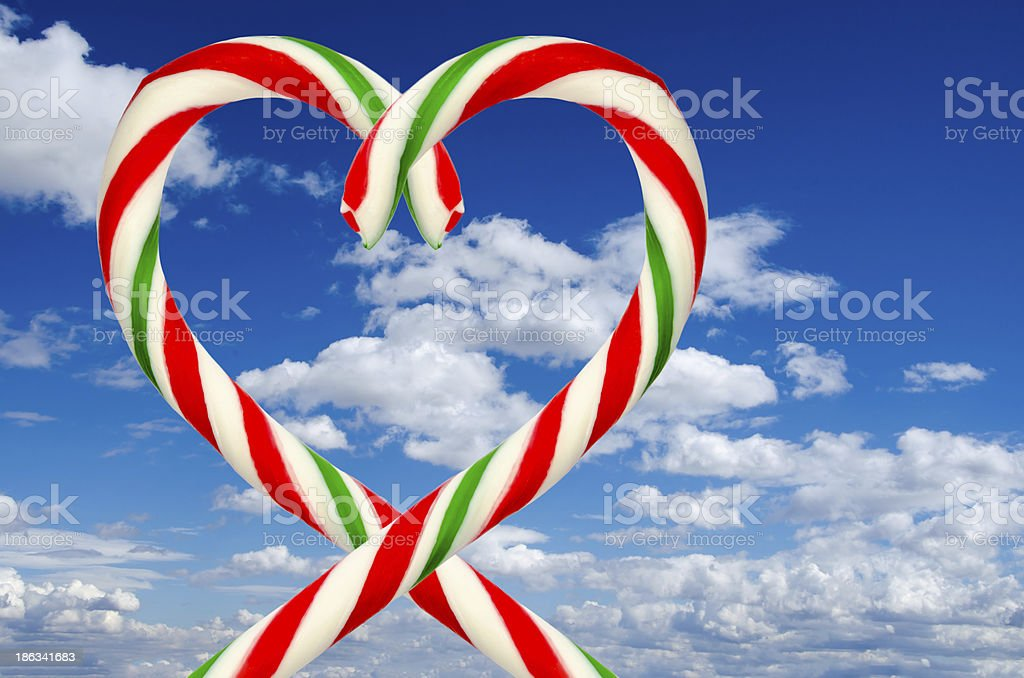 Heart shape of sugar sticks on blue sky and clouds royalty-free stock photo