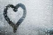 Heart Shape on window glass, it´s raining outside